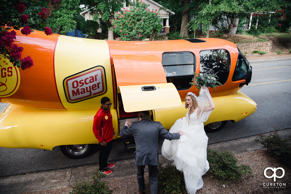 Bride and groom leaving the ceremony in the Oscar Mayer Weinermobile.