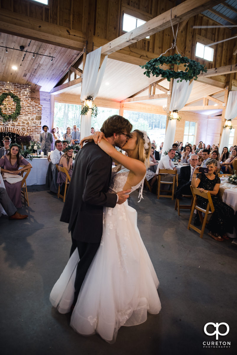 Bride and groom kissing during their first dance at the wedding reception at South Wind Ranch in Travelers Rest,SC.