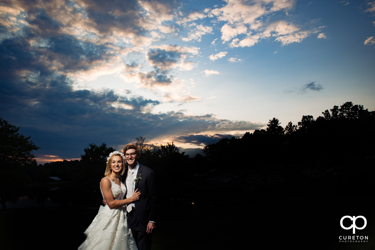 Bride and groom in front of a beautiful sunset at the wedding reception at South Wind Ranch in Travelers Rest,SC.