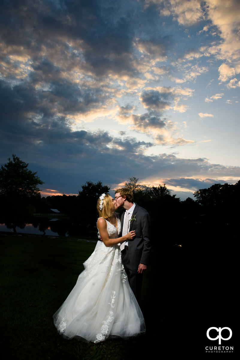 Groom and bride kissing at sunset at the wedding reception at South Wind Ranch in Travelers Rest,SC.
