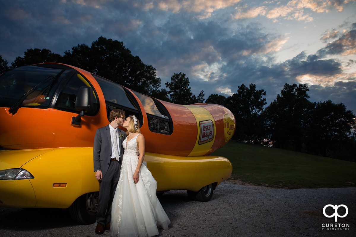 Bride and groom kissing in front of the Oscar Mayer Weinermobile.