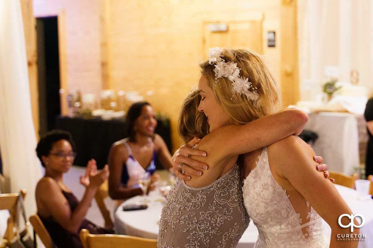 Bride hugging her mom.
