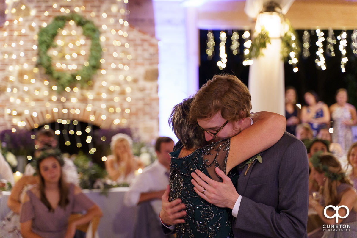 Groom hugging his mom after they danced at the reception.