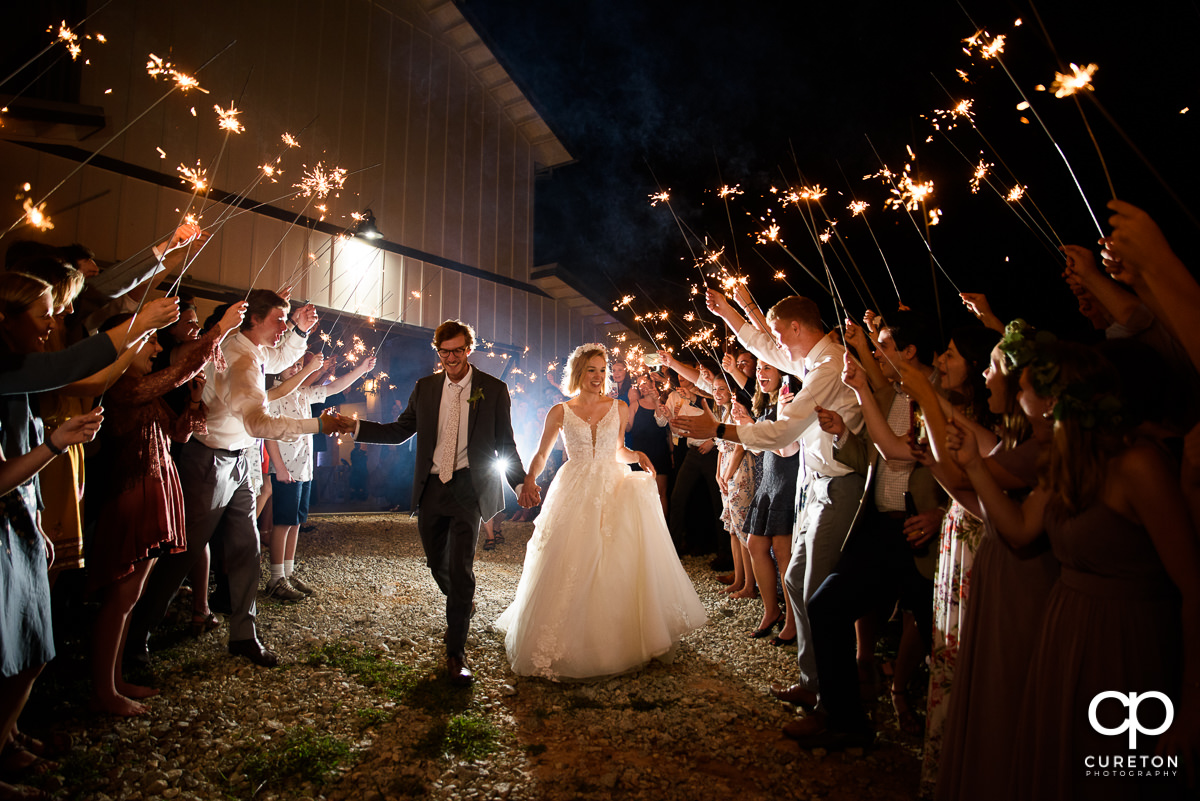 Bride and groom making an exit at the end of the wedding reception at South Wind Ranch in Travelers Rest,SC.