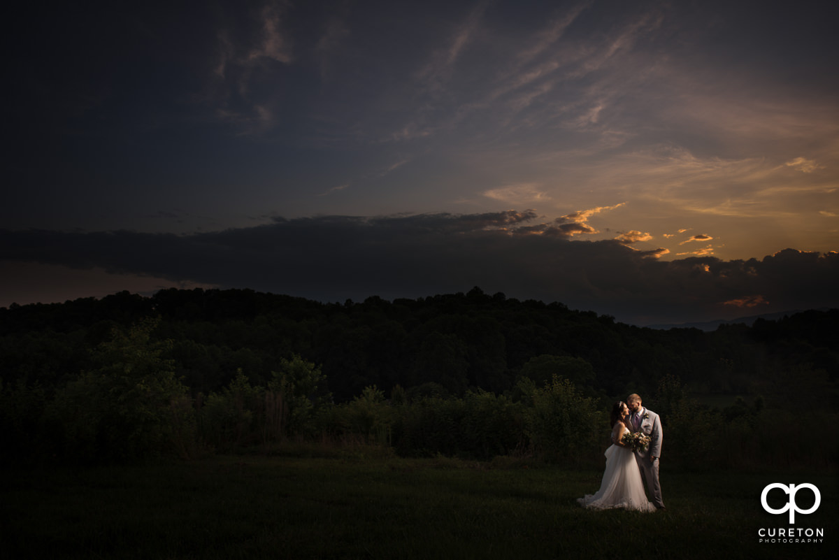 Bride and groom in a field at sunset at their South Wind Ranch wedding.