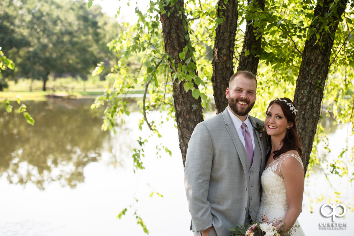 Bride and Groom in front of a pond.