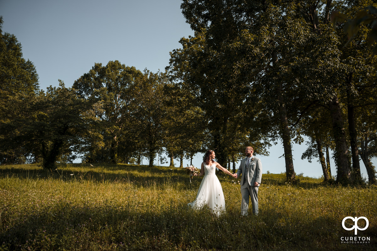Bride walking in a field with groom.