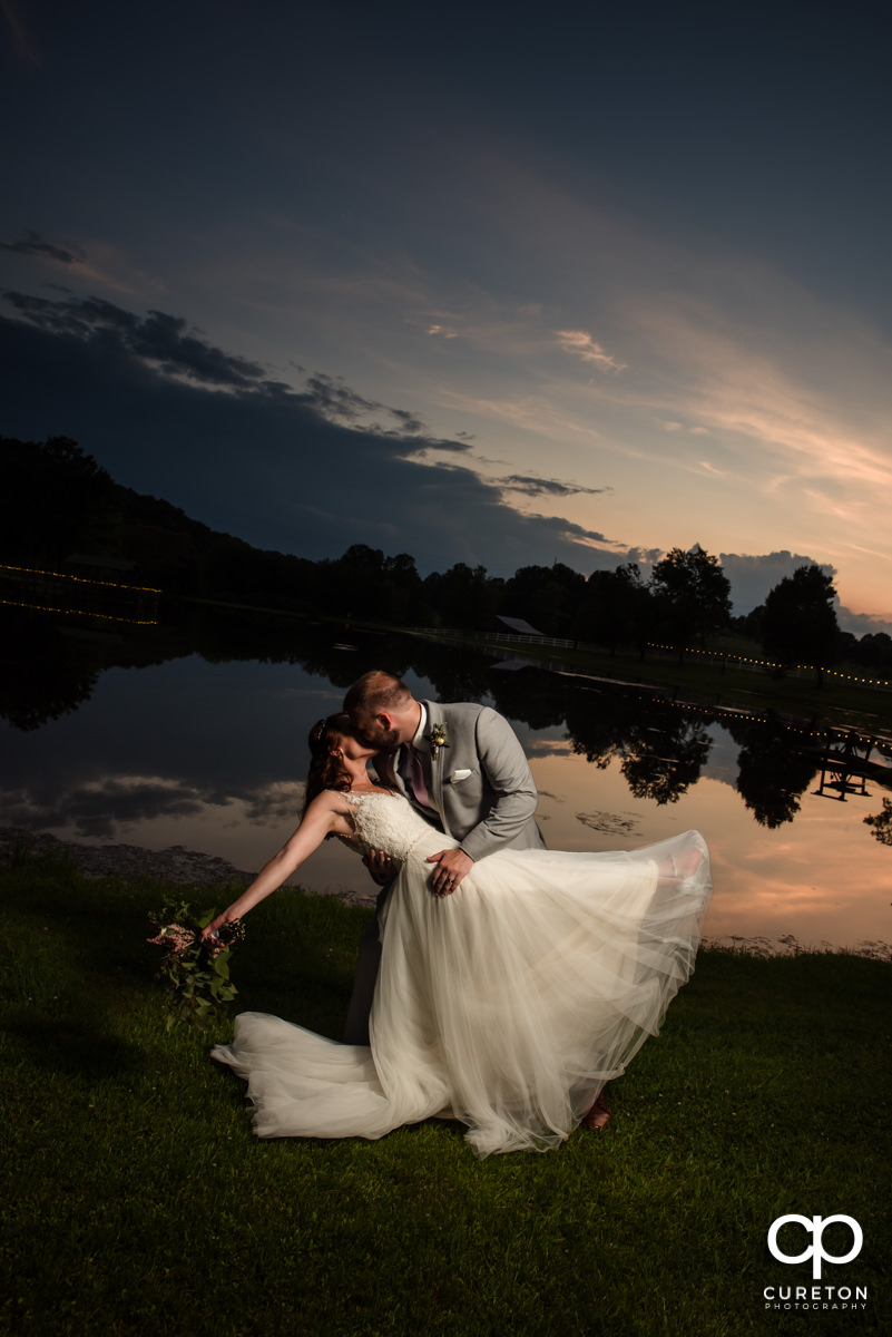 Groom dipping a bride at sunset.