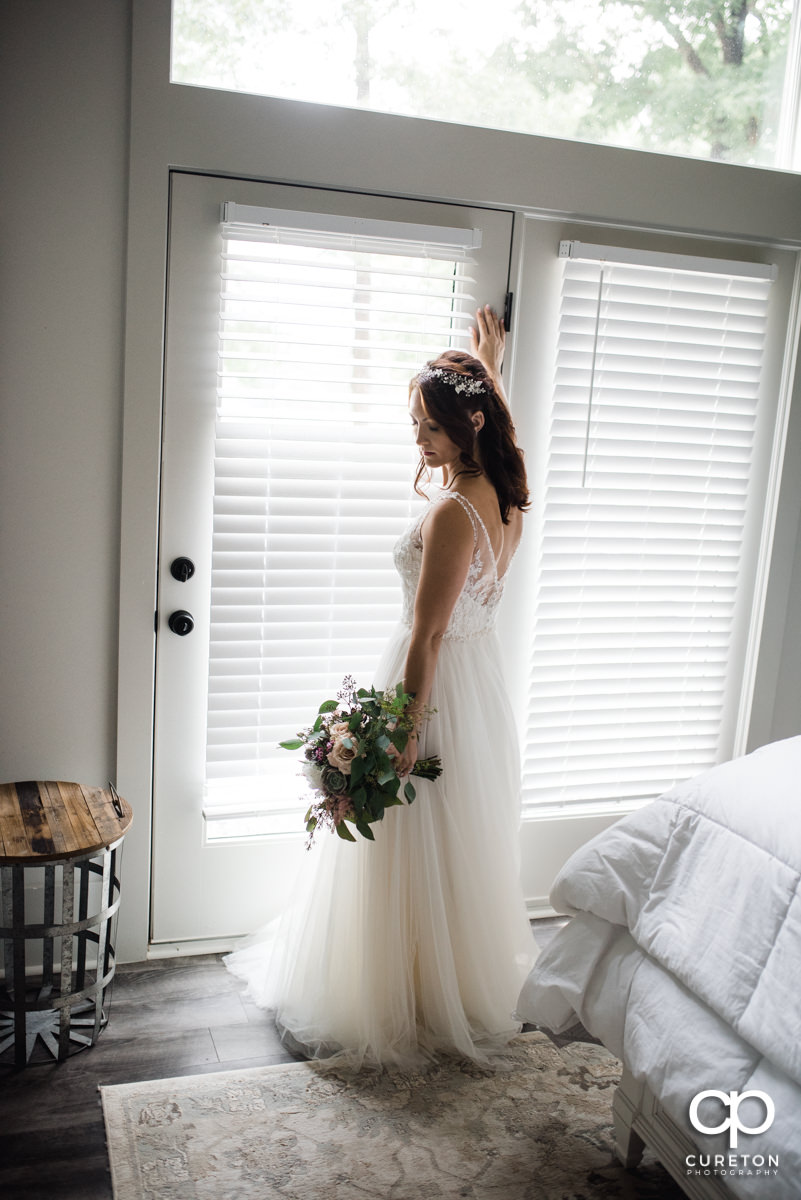Bride standing in a window.