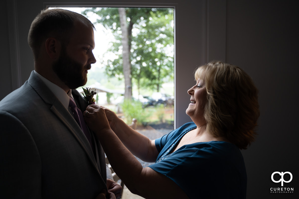 Groom's mom helping him with his boutonniere.