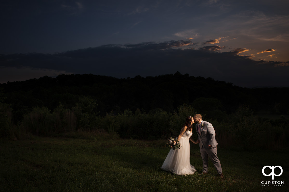 Groom kissing his bride under a sunset sky.