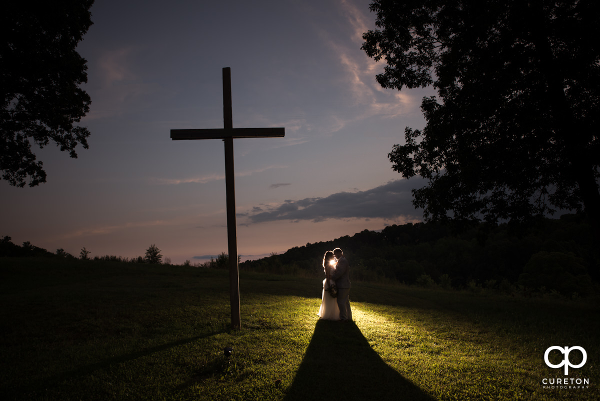 Bride and groom silhouette at sunset beside the cross at South Wind Ranch.