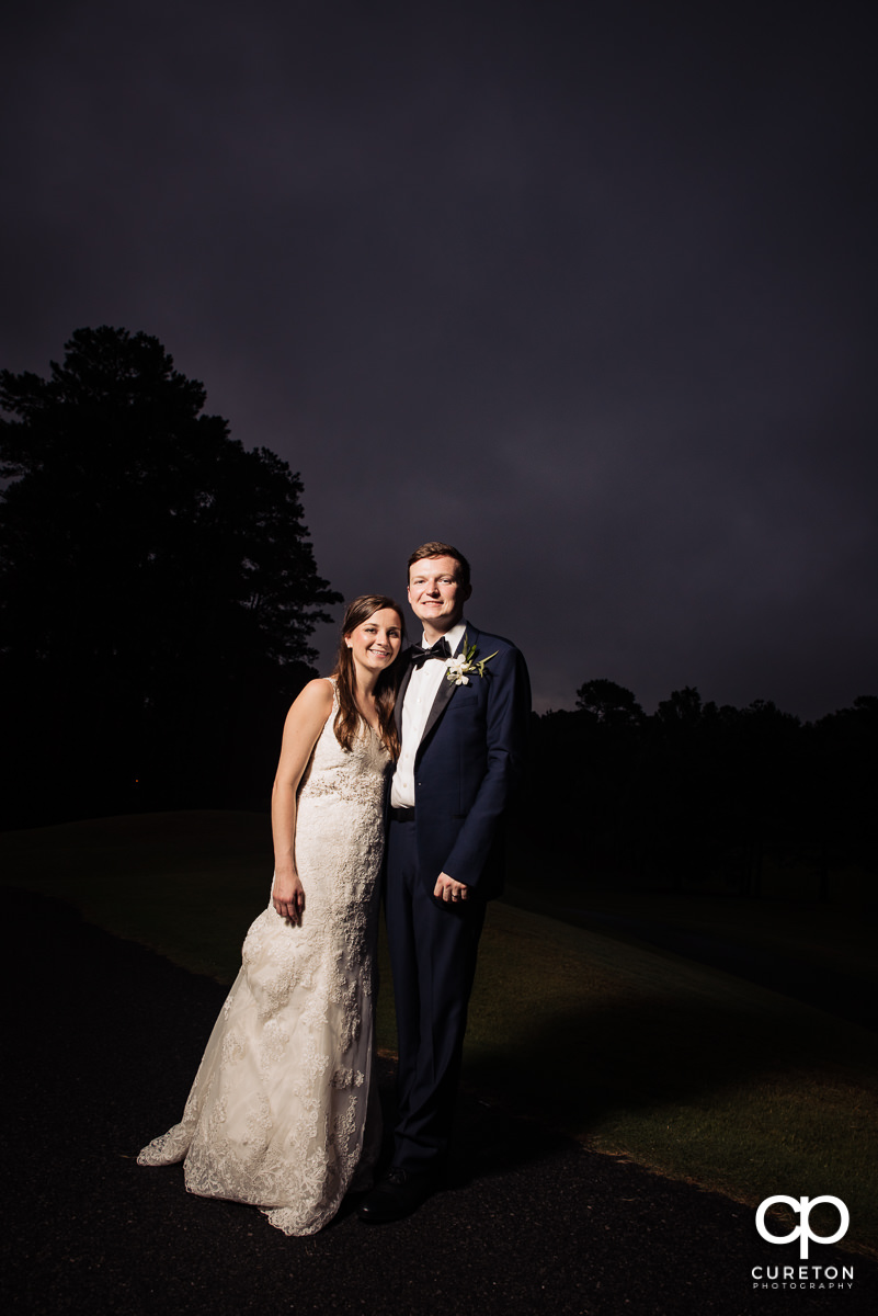 Bride and groom on the golf course at night at their wedding reception at Spartanburg Country Club.