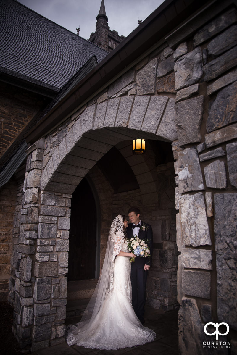 Bride and groom standing in an archway outside of an antique church at their Spartanburg wedding.