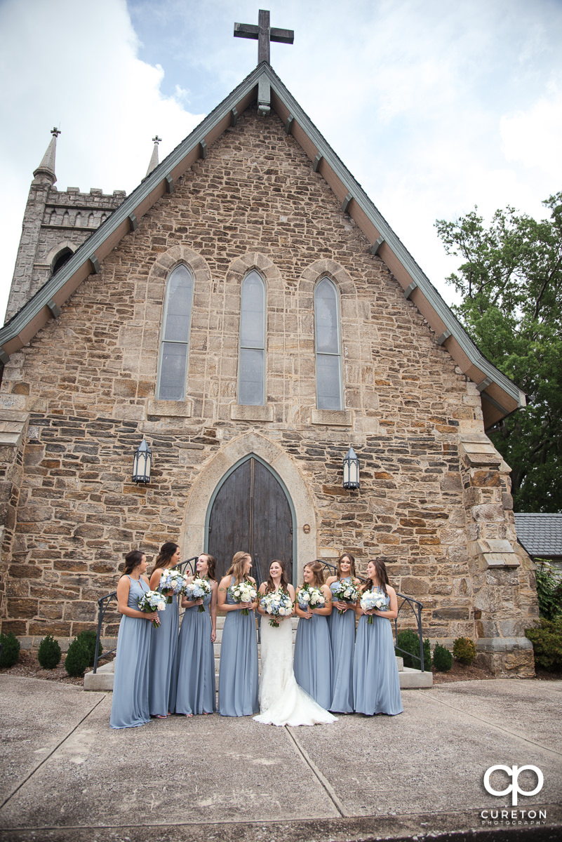 Bride and bridesmaids standing outside of an old church.