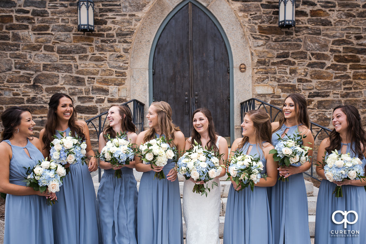 Bride and her bridesmaids laughing before the wedding ceremony,.