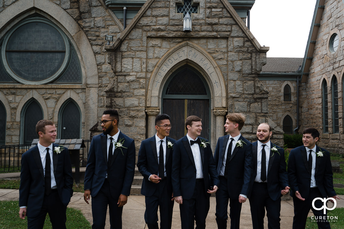 Groom and groomsmen laughing together.