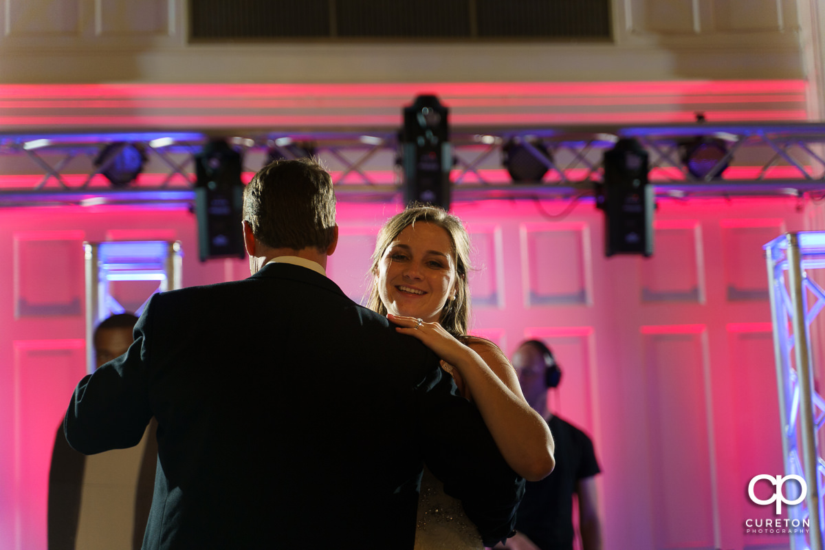 Bride smiling while dancing with her dad.