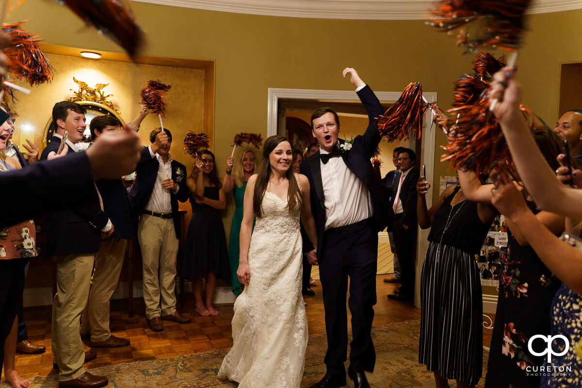 Bride and groom making a grand exit from the wedding reception as guests cheer with Auburn pom poms.