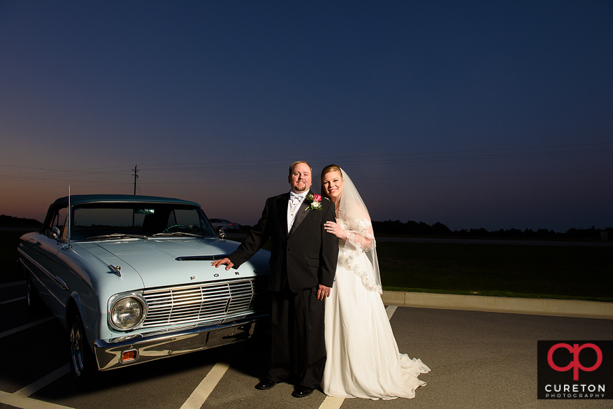 MArired couple posing with a ford falcon after their weddingin Sumter,SC.
