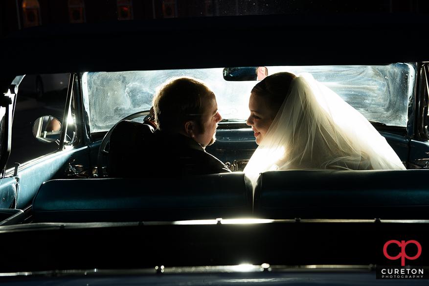 Epic backlit photo of a couple inside a vintage car.