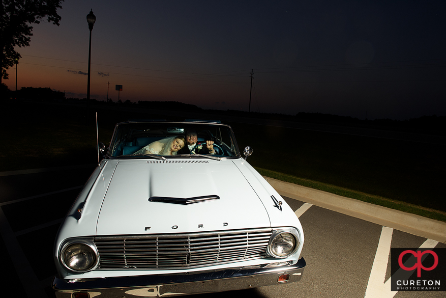 Bride and groom at sunset in a ford falcon vintage car after their wedding.