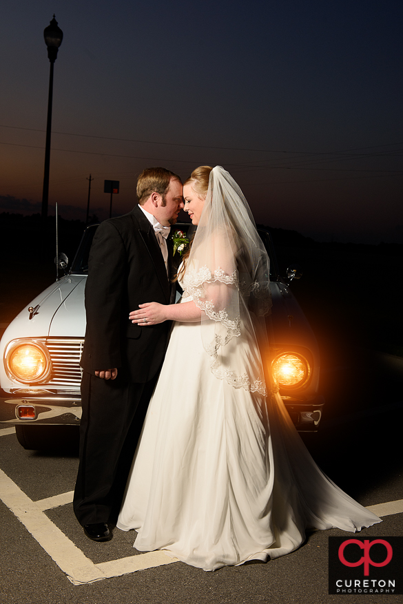 Bride and groom in front of the headlights of a vintage car.