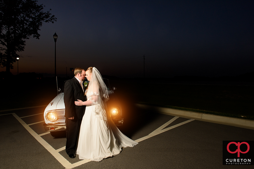 Bride and groom with a vintage car.