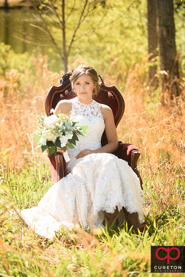 Bride in vintage chair in tall grass at Furman University.