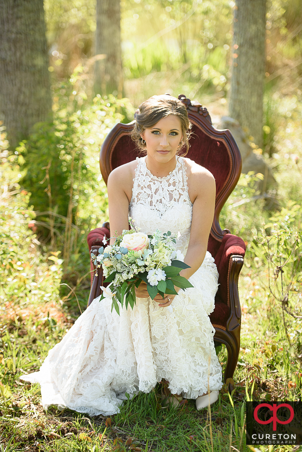 Bride sitting in a victorian chair.