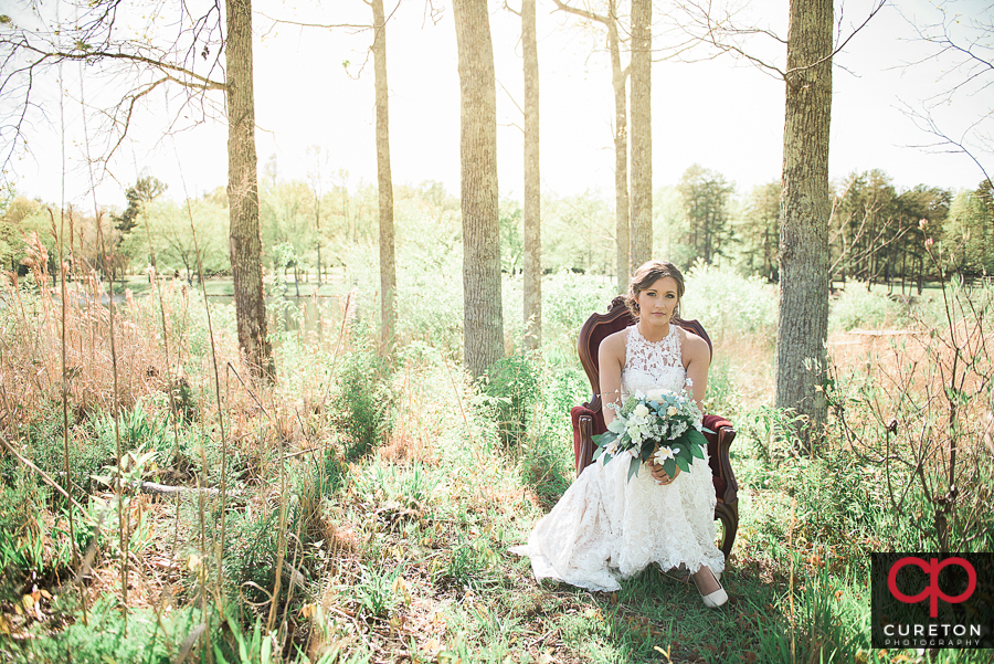 Bride sitting in a field near the Furman lake.