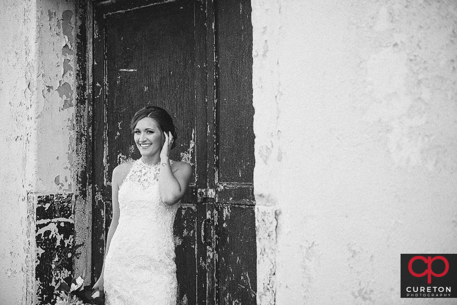 Bride standing in a disheveled doorway at the Taylors Mill.