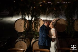 Bride and groom kissing in a winery.