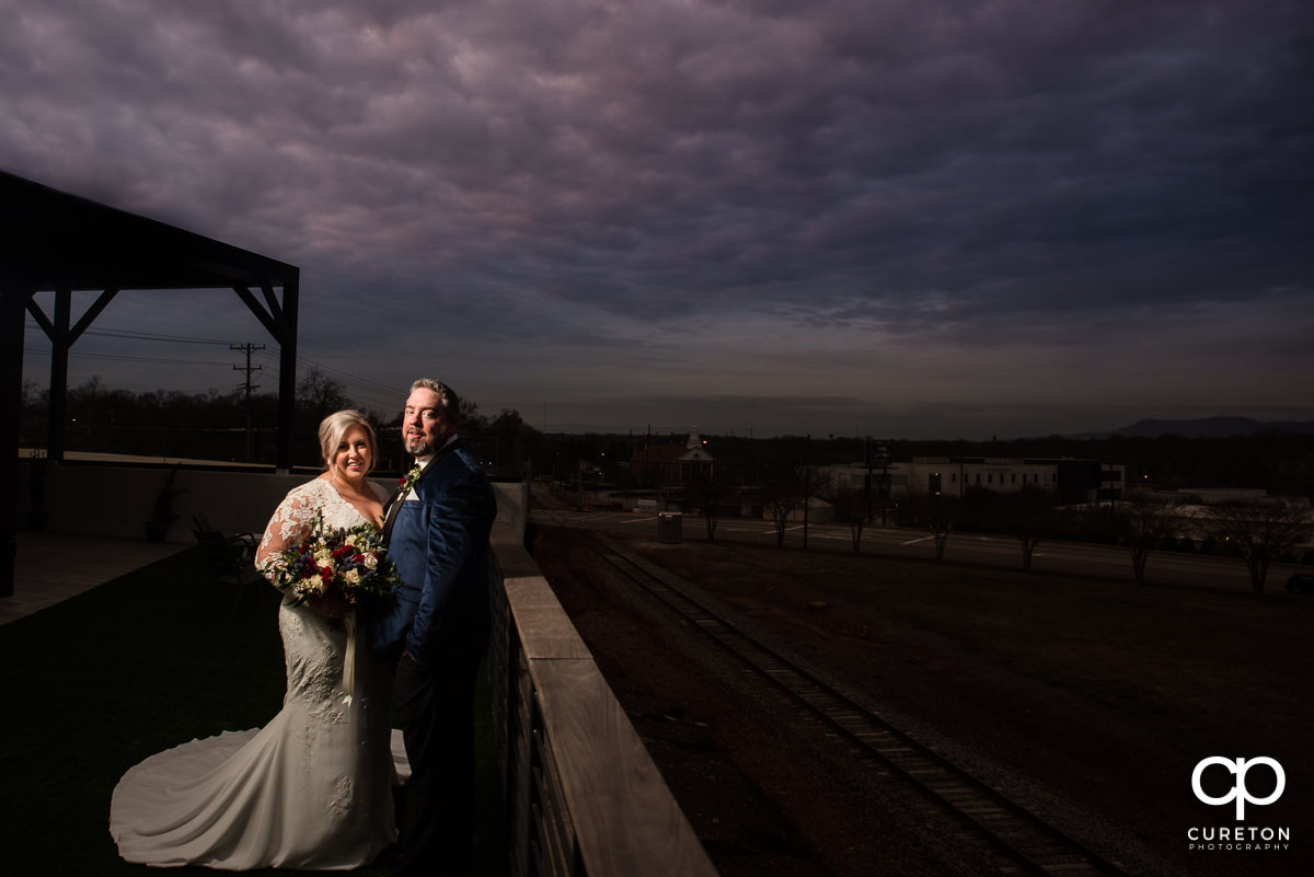 Bride and groom on a rooftop under a purple sky in Greenville.