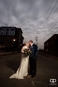 Bride and groom kissing in the middle of the road.