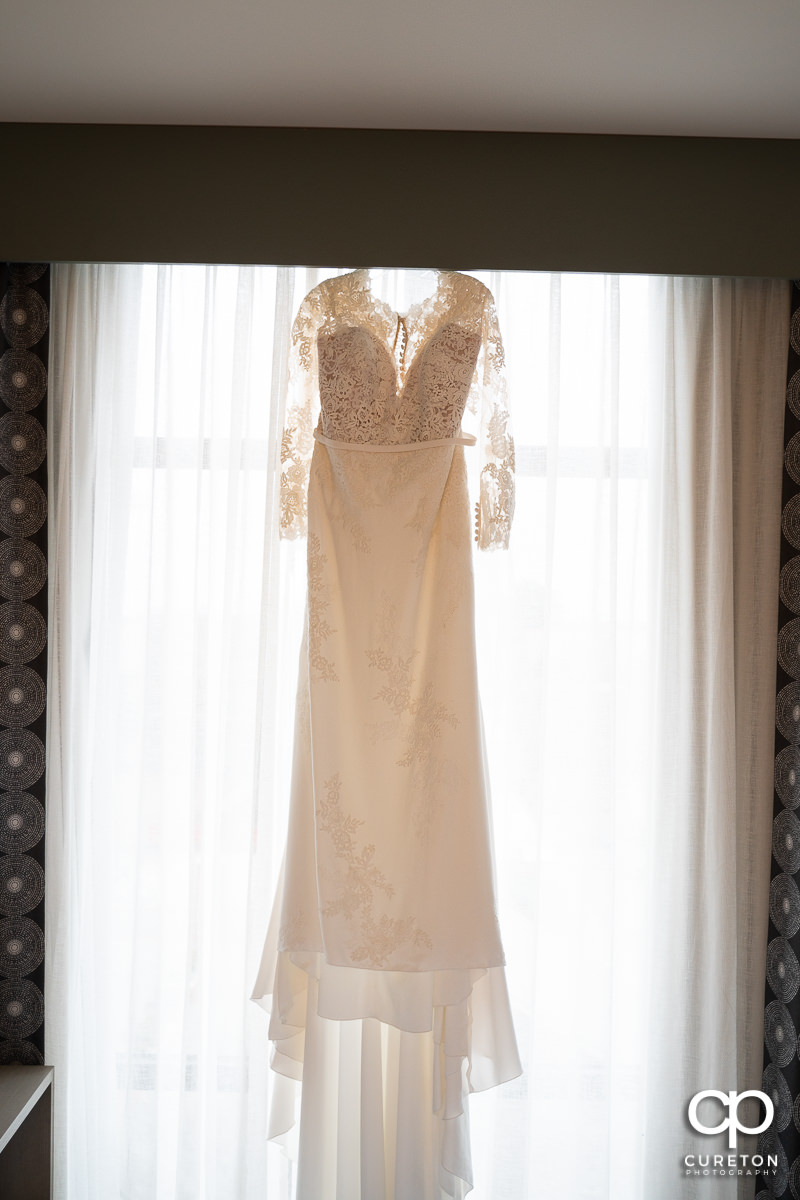 Bride's dress hanging in a hotel window.