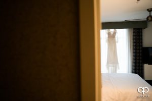 Bride's dress hanging in a hotel room.