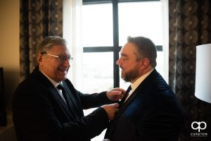 Groom's dad helping him with his tie.