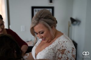 Bride smiling as she puts on her dress.