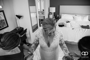 Bride being helped in to her dress.