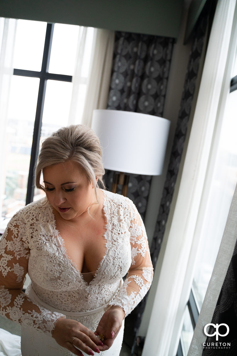 Bride standing in window light.