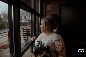 Bride looking out of the winery window.