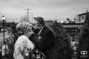 Groom kissing his bride.