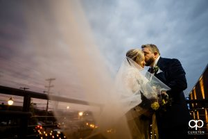 Groom kissing his bride as her veil blows into the wind.