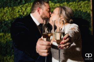 Bride and groom kissing behind champagne glasses.