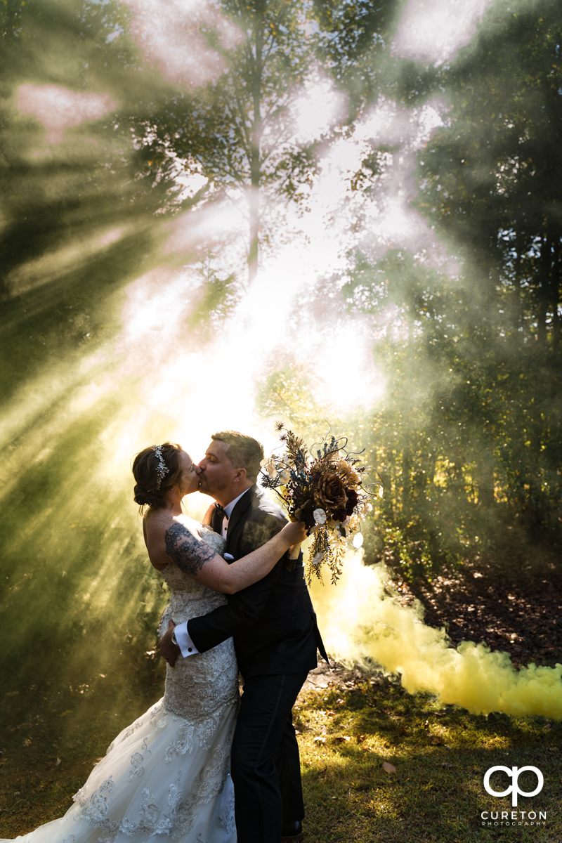 Bride and groom kissing as a yellow smoke bomb goes off at their Viewpoint at Buckhorn Creek wedding in Greenville,SC.