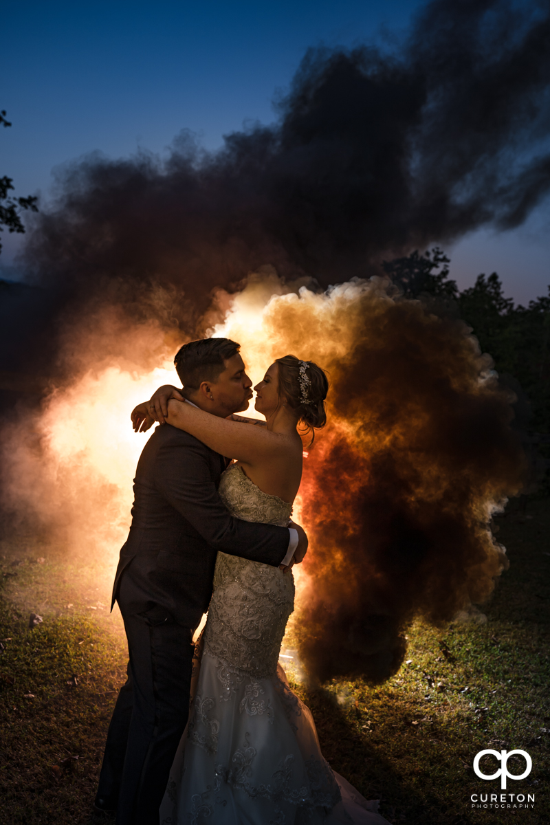 Bride and groom slow dancing at sunset as a smoke bomb goes off in the background at their Viewpoint at Buckhorn Creek wedding in Greenville,SC.