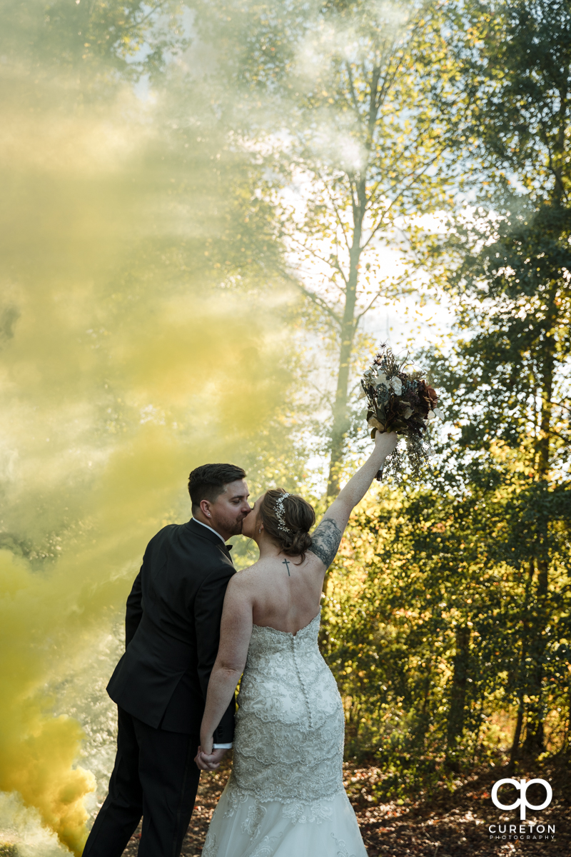 Bride holding her flowers in the air in front of a yellow smoke bomb at her wedding at The Viewpoint at Buckhorn creek.