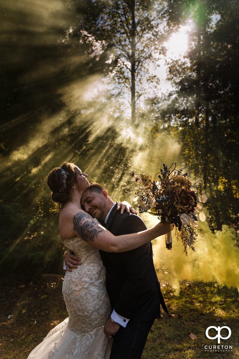 Groom resting his head on his brides chest as they stand in some light rays coming though the leftover smoke of a yellow smoke bomb at their Viewpoint at Buckhorn Creek wedding in Greenville,SC.