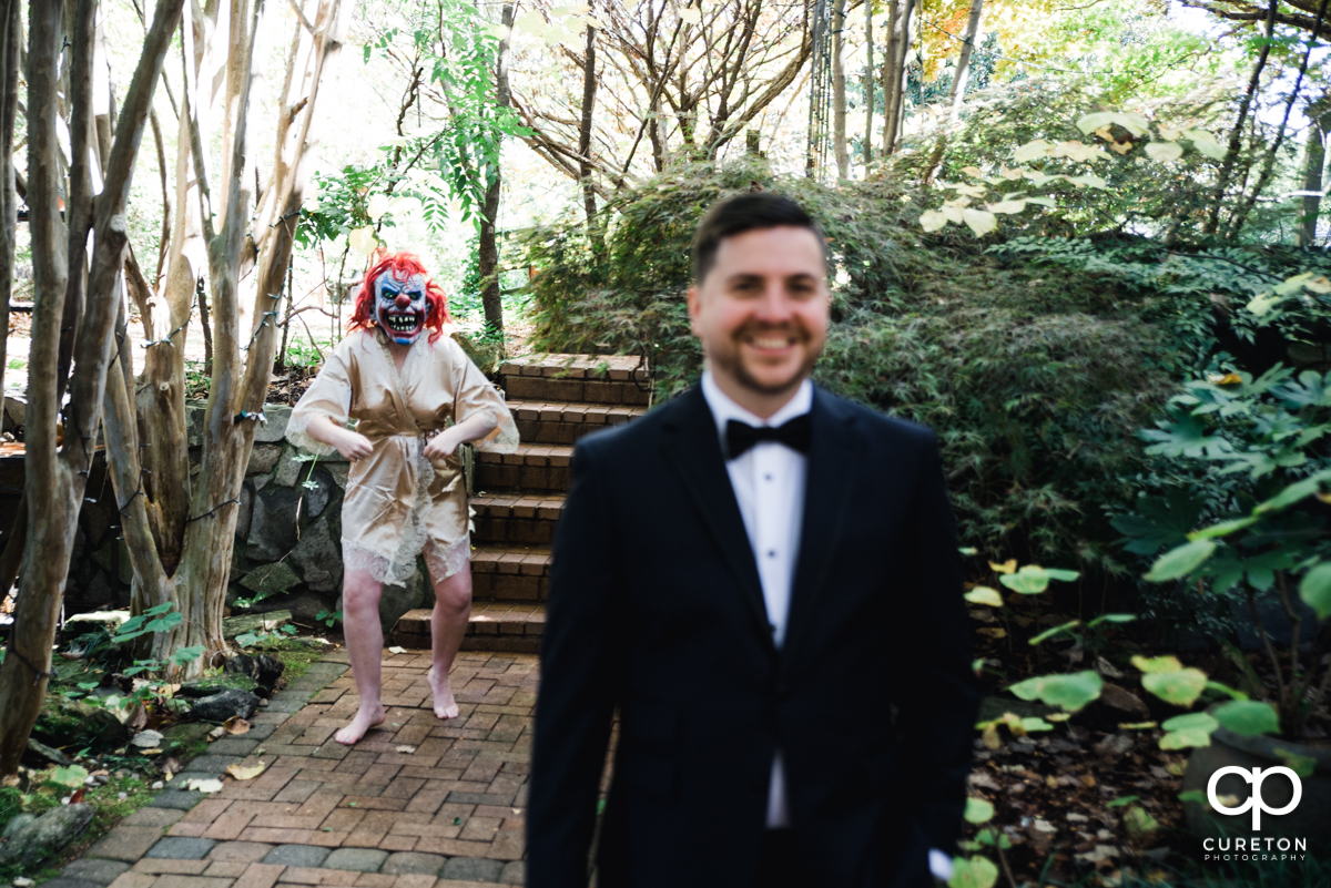 Bride wearing a clown mask sneaking up on her groom at a first look.